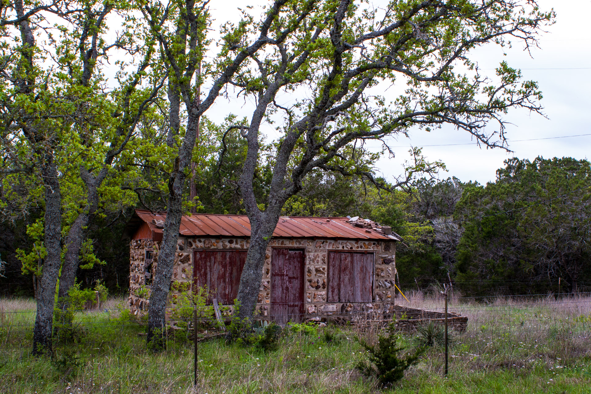 Burnet, Texas - A Red Stone Cottage With Bluebonnets (angle left)