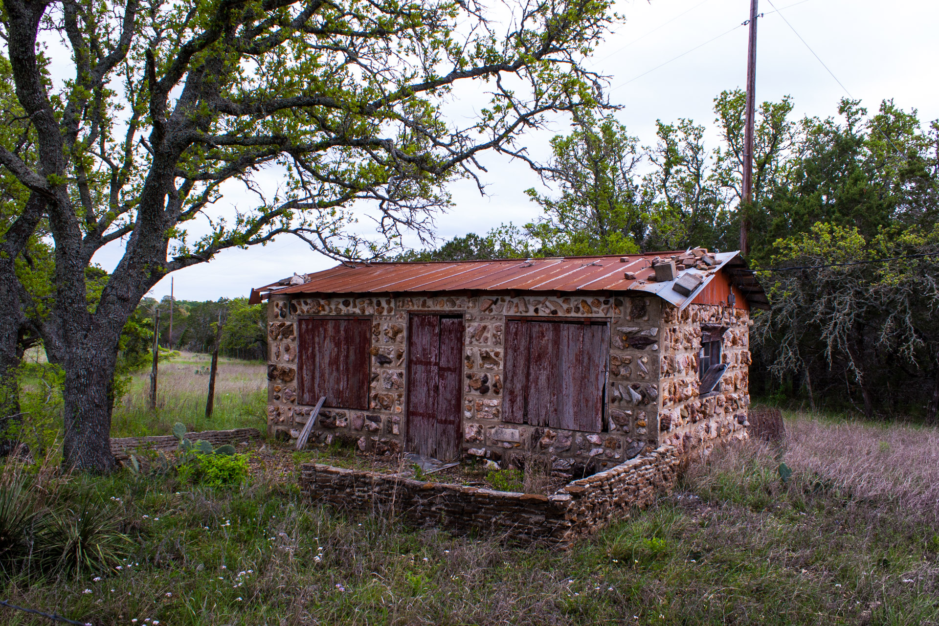 Burnet, Texas - A Red Stone Cottage With Bluebonnets (angle right)