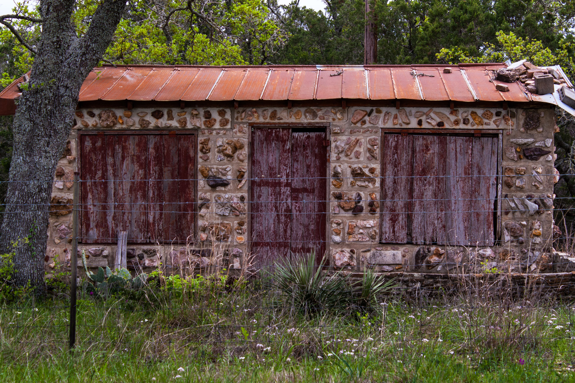 Burnet, Texas - A Red Stone Cottage With Bluebonnets (front close)