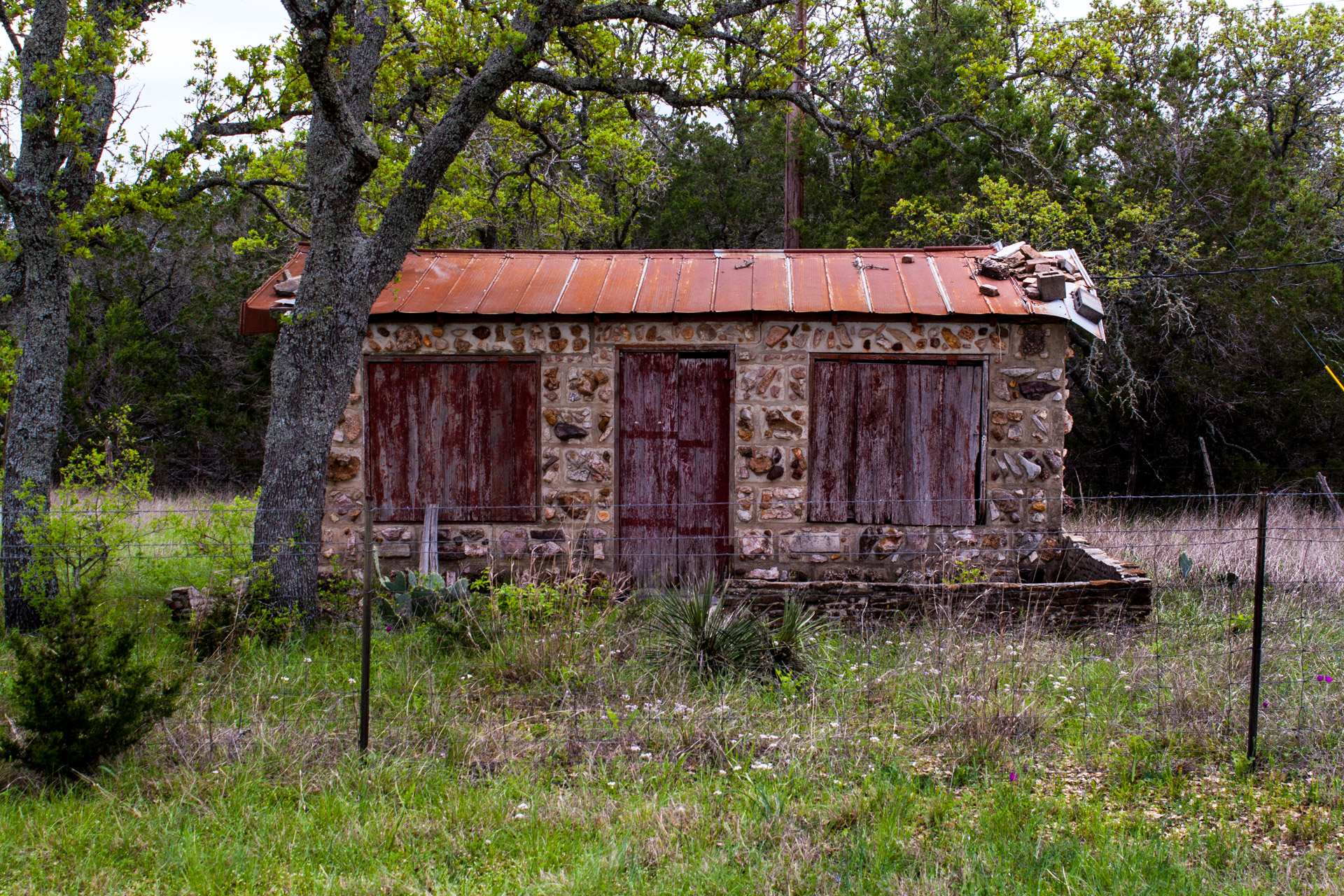 Burnet, Texas - A Red Stone Cottage With Bluebonnets (front mid)
