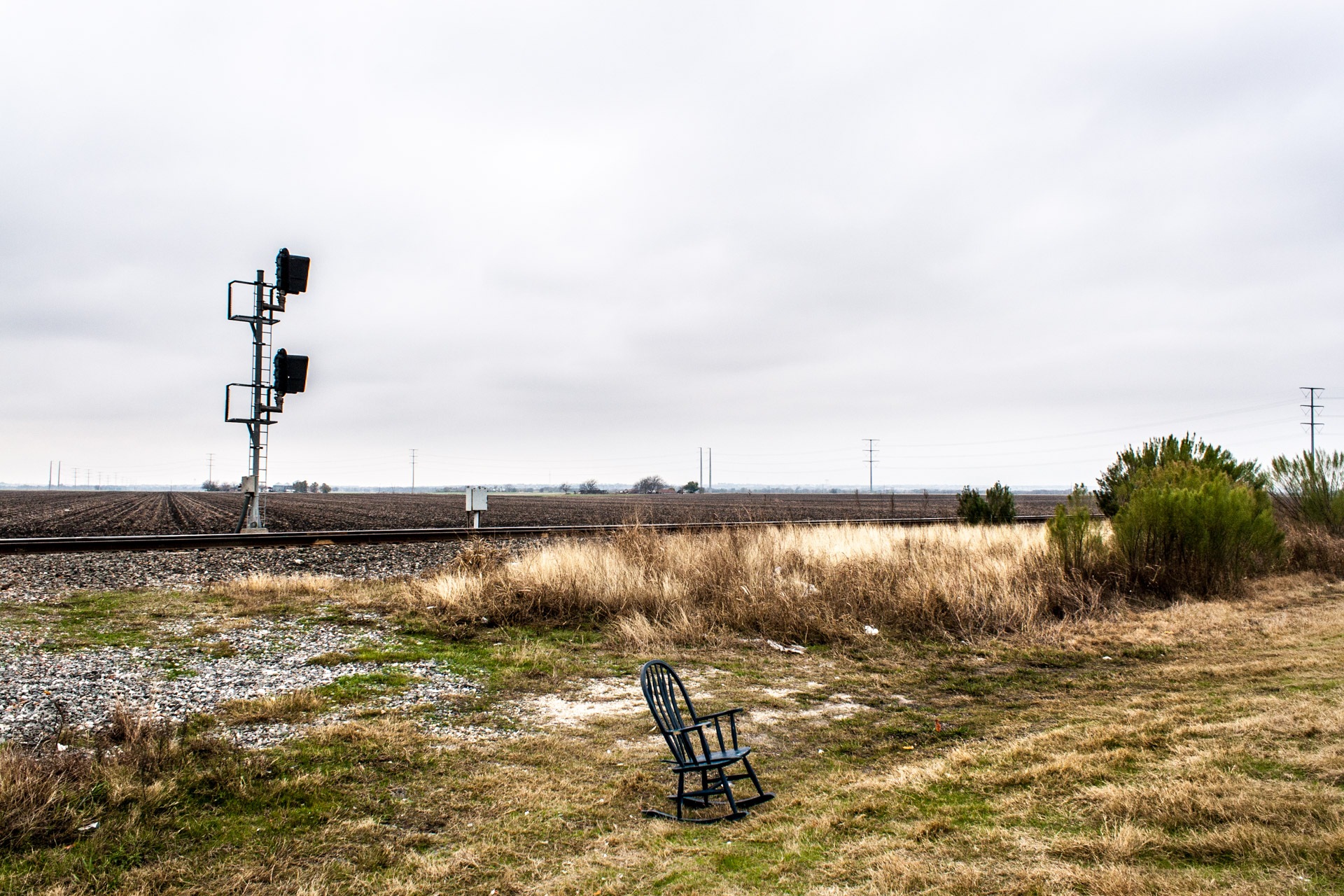Hutto, Texas - A Rocking Chair In Front Of Railroad Tracks
